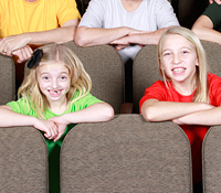 kids sitting in theatre seats smiling