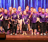 kids in purple t-shirts performing on stage