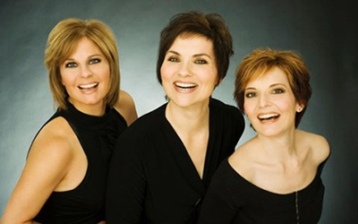 Ann, Sandra, and Barbara Mantini in black dresses with smoke grey background
